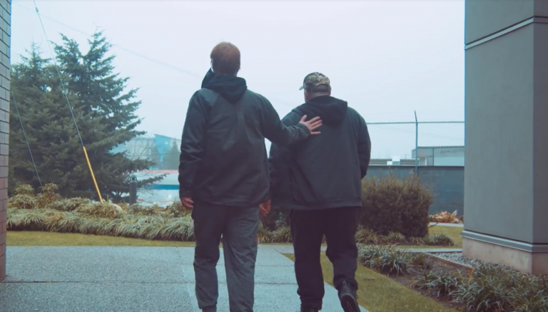 Two men walking outside with their backs facing the camera. One of them is patting the other on the back. It looks cloudy outside, and the men are wearing jackets.