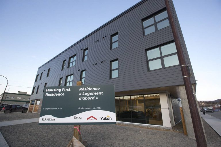 """An image of Whitehorse's first Housing First Residence - a three story apartment building surrounded by clear blue sky and a large sign that says """"Housing First Residence"""" with the Yukon Government logo on it."""