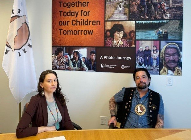 """A man and a woman sit at a wooden table. The woman looks at the camera with a serious expression, and the man has a gentle smile. Behind them there is a flag with the Council of Yukon First Nations logo on it, and photo collage which reads """"Together Today for our Children Tomorrow: A Photo Journey""""."""