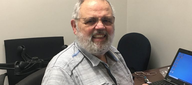 Roy, one of our volunteers, smiles while sitting at his desk holding a black JHS branded notebook. He has a grey beard, short grey hair, and a short sleeve button up shirt.