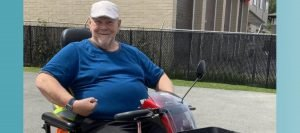 Rob, a 72 year old resident of one of our housing programs, is sitting in his new red scooter outside in a parking lot. He's wearing a blue shirt, a white/grey cap, and is smiling cheerfully at the camera.