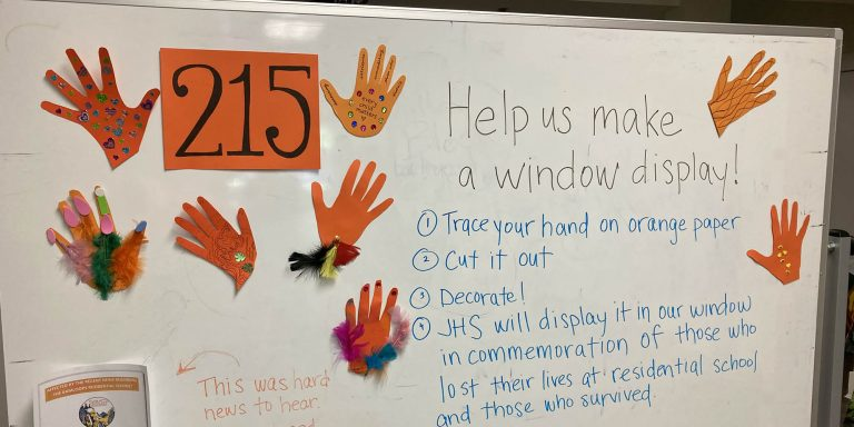 """A photo of a whiteboard at the Vancouver Community Services Office, with several handprints cut out of orange paper, surrounding the number 215 on an orange piece of paper. In marker, the words """"help us make a window display!"""" is seen on the whiteboard, with steps of how to participate in an initiative commemorating the loss of 215 children whose bodies were found at the Kamloops Residential School"""